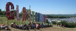 The Glastonbury sign with resting revellers